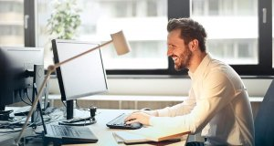 young-man-in-white-shirt-sitting-on-black-rolling-chair-while-facing-computer-set-and-smiling-photo
