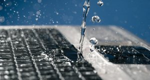 A stream of water pours on the laptop keyboard